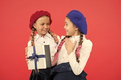 Girl giving gift box to friend. Girls friends celebrate holiday. Children formal wear with gift box. Open gift now stock photography