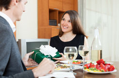 Girl giving gift during romantic dinner Royalty Free Stock Photography