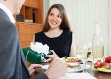 Girl giving gift during romantic dinner Stock Image
