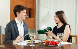 Girl giving gift during romantic dinner Stock Photography