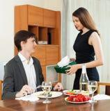 Girl giving gift during romantic dinner Stock Photos