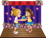 A girl giving gifts to her friend Stock Photos
