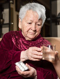Girl giving a glass of water to the sick old woman Stock Photography