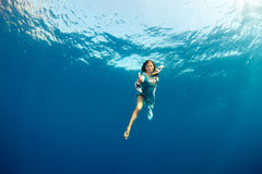 Girl giving hand to you underwater Royalty Free Stock Images