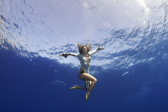 Girl giving hand to you underwater Royalty Free Stock Photography