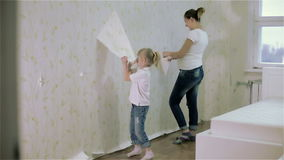 A girl giving a high five to her mother and they remove wallpaper. Slow motion. A blond little girl giving a high five to her pregnant mother and they remove stock video