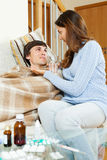 Girl giving  medicament to unwell husband Royalty Free Stock Photos