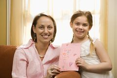 Girl giving mom a drawing. royalty free stock images