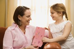 Girl giving mom a drawing. stock image