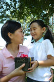 Girl giving mother. Girl smiling and giving mother black gift box Stock Photo