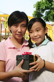 Girl giving mother. Happy girl smiling and giving mother a black gift box Stock Images