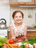 Girl giving a plate of cherries. Many fruits and vegetables on the table in home kitchen interior, healthy food concept Stock Images
