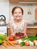 Girl giving a plate of cherries. Many fruits and vegetables on the table in home kitchen interior, healthy food concept Royalty Free Stock Image