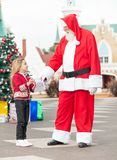 Girl Giving Wish List To Santa Claus Royalty Free Stock Images