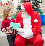 Girl Giving Wish List To Santa Claus Royalty Free Stock Photography