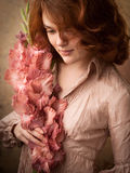 Girl with gladiolus. Red hair Girl with pink gladiolus royalty free stock photos
