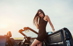 Girl gladly posing next to a black car. Against the sky on a fantastic sunset Stock Photography