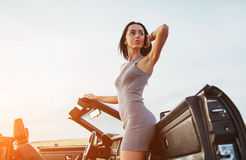 Girl gladly posing next to a black car. Against the sky on a fantastic sunset Royalty Free Stock Image