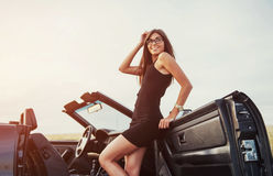 Girl gladly posing next to a black car. Against the sky on a fantastic sunset Royalty Free Stock Images