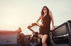 Girl gladly posing next to a black car. Against the sky on a fantastic sunset Royalty Free Stock Photos