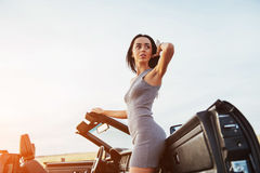 Girl gladly posing next to a black car. Against the sky on a fantastic sunset Stock Photos