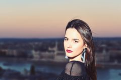 Girl with glamour makeup. Sexy girl with elegant hair. Fashion and beauty of business lady. Luxury woman with view on. Evening city. Modern life with princess royalty free stock image