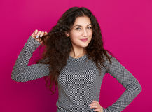Girl glamour portrait on pink, long curly hair Stock Photos