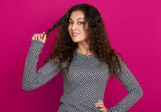 Girl glamour portrait on pink, long curly hair Royalty Free Stock Photo