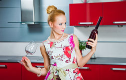Girl with glass and bottle of wine in kitchen Royalty Free Stock Image