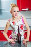 Girl with glass and bottle of wine in kitchen Stock Photography