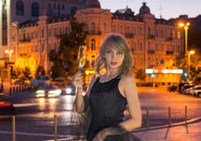 Girl with a glass of champagne in the city Royalty Free Stock Image