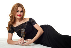 Girl with glass of champagne lying on fur, wearing a black dress. Royalty Free Stock Photos