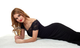 Girl with glass of champagne lying on fur, wearing a black dress. Stock Image