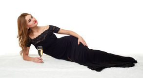 Girl with glass of champagne lying on white fur, wearing a black dress. Royalty Free Stock Photos