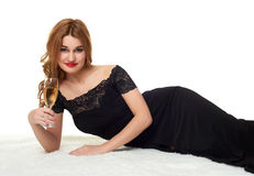 Girl with glass of champagne lying on white fur, wearing a black dress. Royalty Free Stock Photography