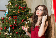 Girl with a glass of champagne on new year's tree Stock Photos