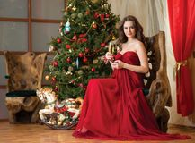 Girl with a glass of champagne on new year's tree Stock Photography