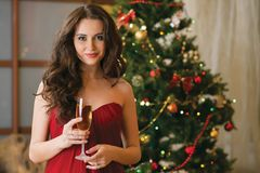 Girl with a glass of champagne on new year's tree Royalty Free Stock Photography