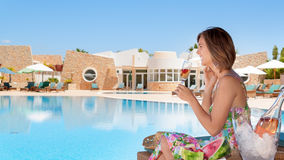 Girl with a glass of champagne by the pool. Stock Images