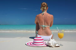Girl with a glass of orange juice on the beach Royalty Free Stock Images