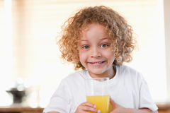 Girl with a glass of orange juice in the kitchen Royalty Free Stock Image