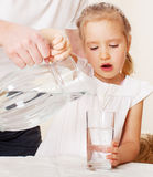 Girl with glass pitcher water. Child with glass pitcher water. Little girl drinking water at home Stock Images