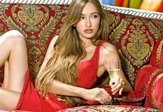 Girl with glass of wine. Beautiful blonde woman on the sofa with glass of champagne stock image