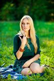 Girl on the grass with a glass of wine royalty free stock image