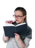 Girl in glasses. Intent looking girl in glasses write in book. white background stock photos