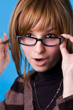 Girl in glasses. Isolated on blue background Stock Images