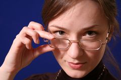 Girl in glasses. The girl in glasses, on a dark blue background Royalty Free Stock Photography