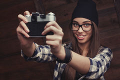 Girl in glasses and braces with vintage camera. Hipster girl in glasses and black beanie with vintage camera making a selfieshot on the wooden background Stock Photos