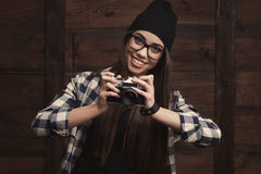 Girl in glasses and braces with vintage camera. Hipster girl in glasses and black beanie with vintage camera on the wooden background Stock Photos