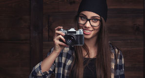 Girl in glasses and braces with vintage camera. Hipster girl in glasses and braces with vintage camera on the wooden background Royalty Free Stock Photography